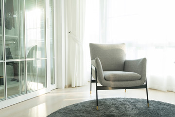 Modern grey armchair next to bed with grey pillows in bedroom interior