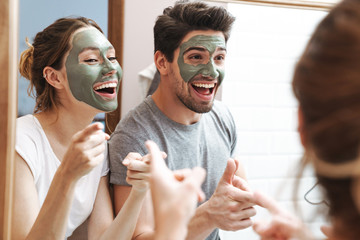 Image of cheerful couple standing in bathroom with face mask