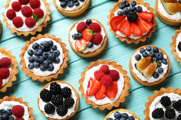 Many different berry tarts on blue wooden table, flat lay. Delicious pastries