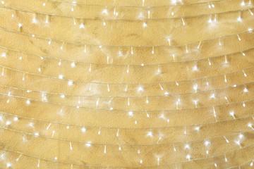 Christmas lights hanging on beige stone wall