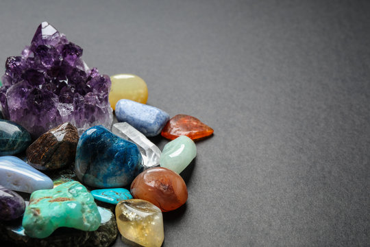 Different gemstones on dark table, space for text