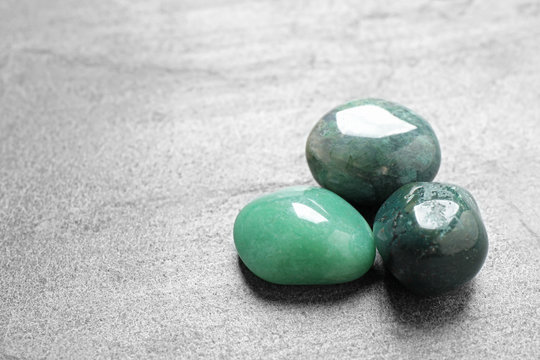 Beautiful green gemstones on grey table, space for text