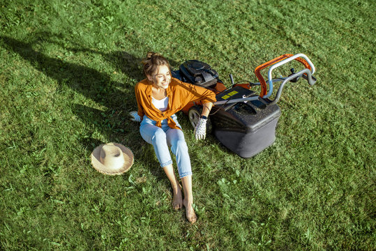 Beautiful young woman resting on the grass near the lawn mower enjoying gardening on the backyard in the countryside