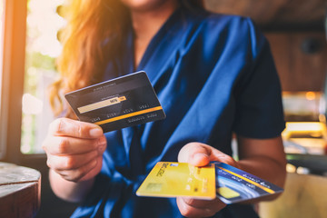 Closeup image of a woman holding and giving credit card to someone