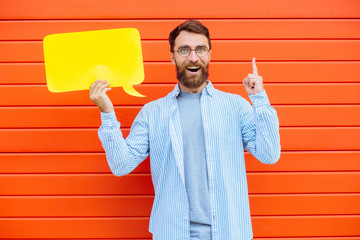 Productive , generative beard man with many cool ideas on head holding yellow paper bubble speech on red background outdoor.