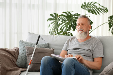 Blind mature man reading book written in Braille at home