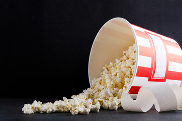 Tickets, big bucket of tasty popcorn.Concept of movie theater.Empty black spce for text