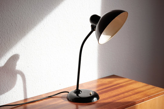 an antique black table lamp from the 20s bauhaus era standing on an old desk commode isolated on white background very rare in original condition design icon close up living room minimalistic design