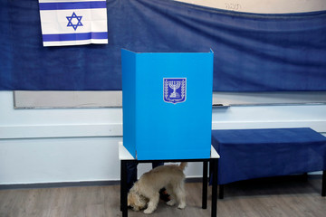 A dog stands next to it's owner behind a voting booth as Israelis vote in a parliamentary election at a polling station in Rosh Ha'ayin, Israel