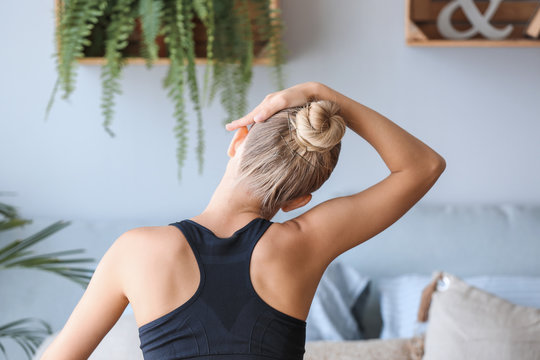 Young woman training at home, back view