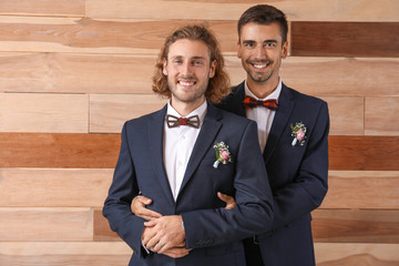 Portrait of happy gay couple on their wedding day against wooden background