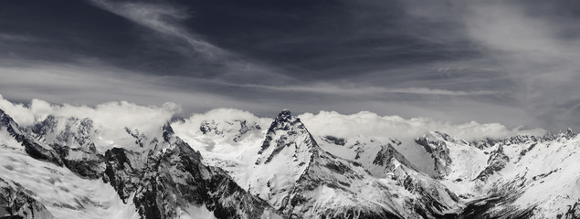 Fototapete - Panorama of snowy winter mountain in sunlit clouds