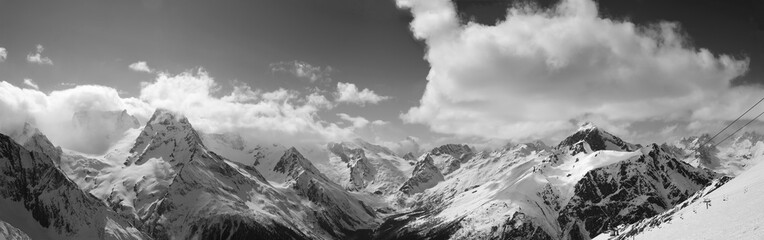 Black and white panorama of snowy sunlit mountains