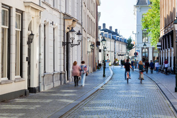Street with historical buildings and motion blur pedestrians