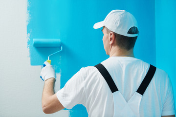 Painter worker with roller painting wall surface into color