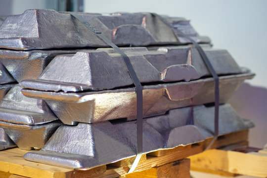 Aluminum ingots are on pallets. Aluminium production. Metalworking. Sale of metal ingots. Metal for production purposes.