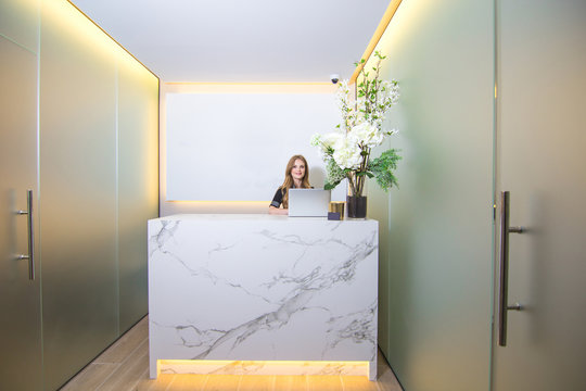 Reception of a modern clinic with a beautiful and smiling woman behind the counter.