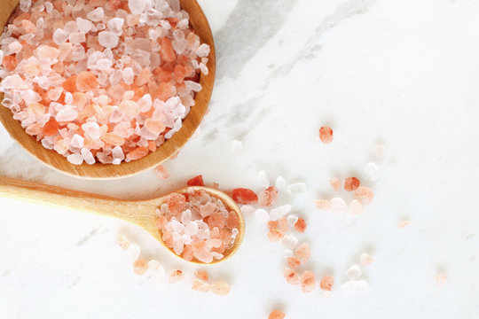 top view of himalayan pink rock salt in wooden bowl and spoon on white marble table.