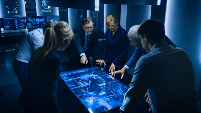 Team of Government Intelligence / FBI Agents Standing Around Digital Touch Screen Table and Tracking Suspect Vehicle Using Satellite Surveillance in the Monitoring Room.