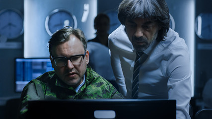 Government Chief of Cyber Security Has Problem Solving Discussion with Military Officer who Works on Computer. Specialists Working on Computers in System Control Room.