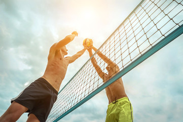 Beach Volleyball players in sunglasses in action with ball under