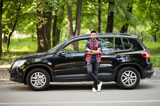 Young handsome indian man standing near his car on the road