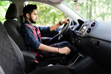 Young indian man in a business suit in the car changes gear