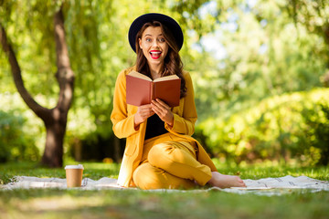 Fototapete - Portrait of her she nice-looking attractive lovely charming pretty trendy cheerful cheery excited crazy overjoyed wavy-haired girl sitting on cover reading cool interesting book on fresh air outdoors