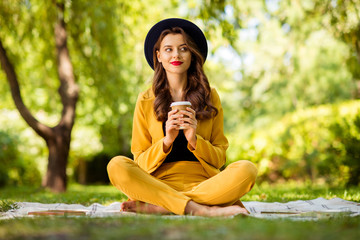 Fototapete - Portrait of her she nice-looking attractive lovely charming gorgeous pretty dreamy peaceful calm wavy-haired girl sitting in lotus position drinking latte cacao on fresh air outdoors