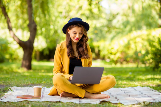 Portrait of her she nice-looking attractive lovely trendy pretty cheerful focused wavy-haired girl sitting in lotus pose studying remotely in green park outdoors
