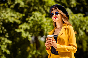 Fototapete - Low below angle view portrait of her she nice-looking gorgeous winsome attractive lovely pretty cheerful trendy fashionable girl holding hot coffee in hands on fresh air in green forest wood outdoors