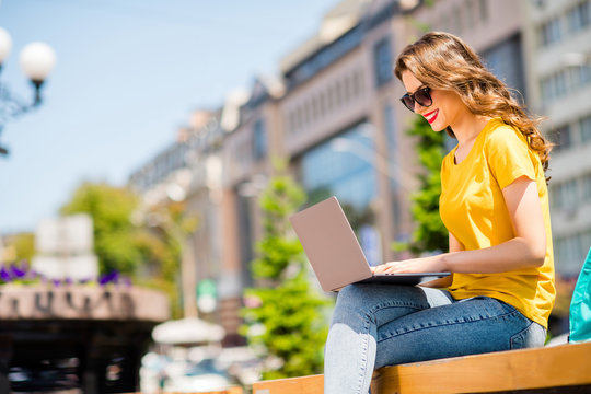 Profile side view portrait of her she nice attractive lovely pretty cheerful cheery confident girl working remotely on digital laptop creating presentation downtown on fresh air outdoors