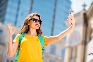 Fototapete - Low below angle view portrait of her she nice attractive lovely winsome pretty cheerful cheery positive girl taking making selfie showing ok-sign ad advert study abroad downtown outdoors
