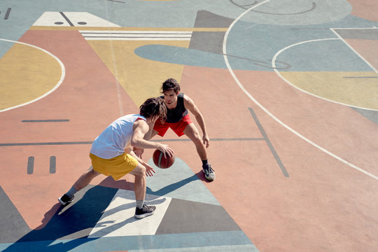 Top view of two sporty men playing basketball on playground in morning .