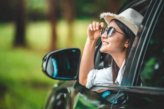 Happy woman hand holding hat outside open window car with green forest woods mountain background. People lifestyle relaxing as traveler on road trip in holiday vacation. Transportation and travel