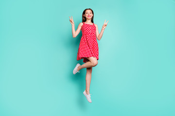 Full size photo of pretty lady making v-signs smiling wearing dotted skirt dress isolated over green, teal turquoise background