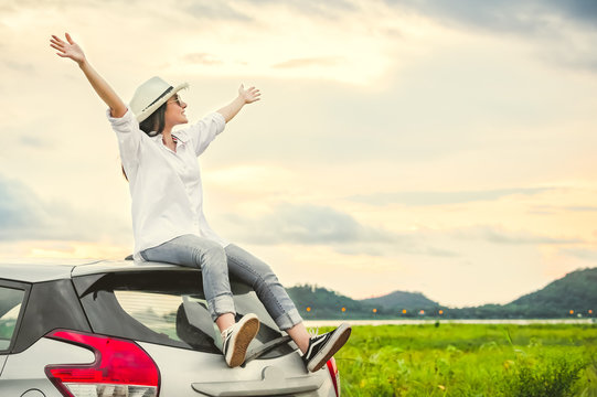 Happy Asian woman spread arms widely and breathed fresh air with happiness mood in evening after sunset on car roof. People lifestyle in long vacation trip concept. Outdoors nature and transportation