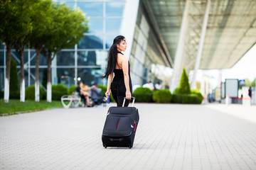 Young Cheerful Woman With a Suitcase. The Concept of Travel and work
