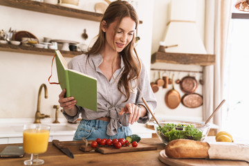 Pretty lady indoors at the kitchen cooking holding notebook.