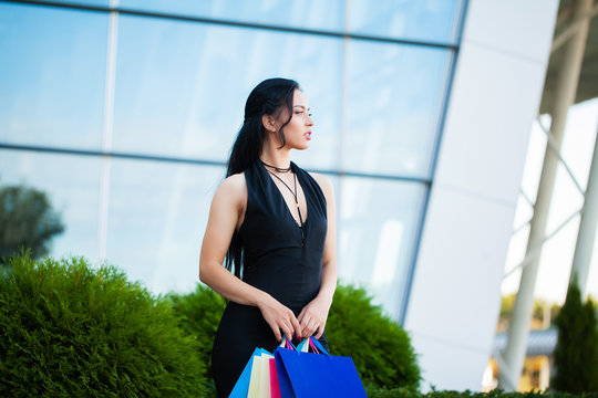 Shopping. Woman holding colored bags near her shooping mall in black friday holiday