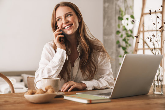 Business woman sit indoors in office using laptop computer taking by mobile phone.
