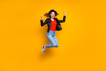 Full length photo of delighted crazy lady raise her fists scream yeah jump celebrate victory wear denim jeans good clothes isolated over yellow color background