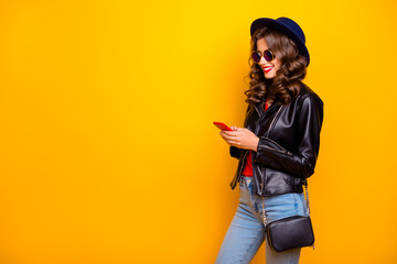 Fototapete - Profile side photo of cute sweet cheerful girl use her cellphone share post social network read feednews wear good black outfit denim jeans isolated over yellow color background