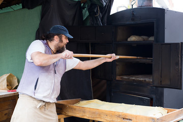 Fototapete - baker puts bread on the shovel into the oven