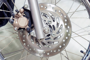 Close-up of a disc brake on a motorcycle.