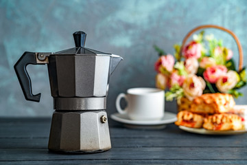 Mocha coffee maker, flowers and sweets on dark background for coffee time