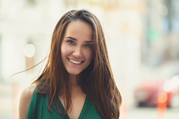 Young pretty likable cheerful woman posing summer city outdoor. Beautiful self-confident girl dressed in emerald-colored jumpsuit with long brown hair walking street enjoing her life, urban lifestyle