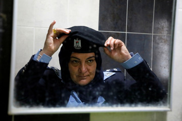 Palestinian traffic police officer Samar Fatafta, 44, is reflected in a mirror as she adjusts her hat in a police station in Ramallah in the Israeli-occupied West Bank