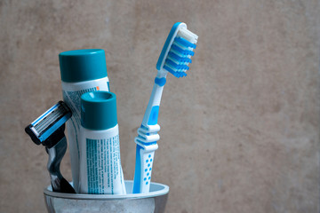Toothbrush with toothpaste and razor in a silver mug