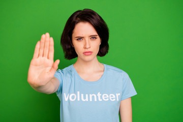 Close-up portrait of her she nice attractive sullen content girl wearing blue t-shirt showing palm stop destruction poverty isolated over bright vivid shine vibrant green background